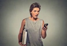 Nxious que mira a la mujer joven que protagoniza el teléfono celular que ve malas noticias o las fotos Imagen de archivo