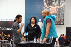 NXT格斗泰勒微风与拿着智能手机的爱好者谈话手中 库存照片