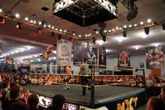 NXT-brottningen Hideo Itami hoppar av det bästa repet in mot motståndare Arkivbild