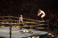 NXT male wrestler Finn Balor fights with Adrian Neville on ring. SAN JOSE - MARCH 27: NXT male wrestler Adrian Neville stands on top of ring ropes with Finn Royalty Free Stock Photo