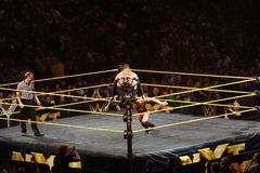 NXT male wrestler Finn Balor squats on top of ring ropes as Adri. SAN JOSE - MARCH 27: NXT male wrestler Finn Balor squats on top of ring ropes as Adrian Neville Stock Image