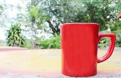 Ny övre morgon för röd kopp på tabellen royaltyfri bild