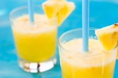 Ny ananasfruktsaft på en blå bakgrund Fotografering för Bildbyråer