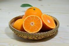 Ny apelsin i korg på den vita tabellen Royaltyfri Foto