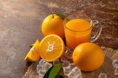 Ny apelsin och ett exponeringsglas av orange fruktsaft på en trätabellbackg arkivbild
