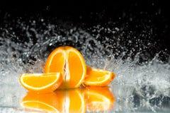 Ny apelsin på svart bakgrund med tryckning av vatten på det mir Arkivfoto