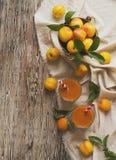 Ny aprikosfruktsaft i exponeringsglas på trätabellen, selektiv fokus Arkivbild
