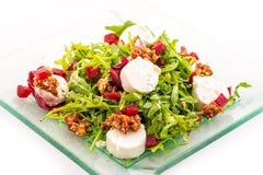 Ny arugulasallad med rödbeta, getost och valnötter på den glass plattan som isoleras på vit bakgrund, produktfotografi för beträf Arkivbild