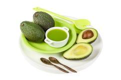 Ny avokado med fruktsaft på den isolerade plattan Royaltyfri Foto