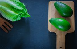 Ny avokado på en skärbräda med grönsallatsidor på en träbakgrund sund mat kopiera avstånd royaltyfri fotografi