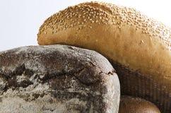 Ny bakad hög av olika sorter av bröd mot den vita väggen royaltyfria bilder