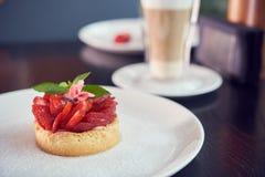 Ny bakad hemlagad paj med jordgubbar och piskad kräm och kanel på den vita plattan Närbild Överkant eller över huvudet sikt royaltyfria foton