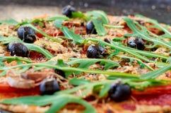 Ny bakad varm pizza på det svarta bakgrundsslutet upp Vegetarisk pizza med grönsaker, svarta oliv och rucola Arkivbilder
