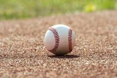 Ny baseballboll på rött spårgummi arkivbild