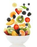 Ny blandad fruktsallad som faller in i en bunke av sallad Royaltyfri Fotografi
