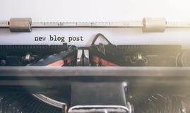 Ny bloggstolpe för ord som är skriftlig på den manuella skrivmaskinen royaltyfri foto