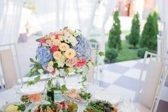 Ny blom- sammansättning på ferietabellen Beautifully organiserad händelse - tjänade som banketttabeller som är klara för gäster Arkivfoton