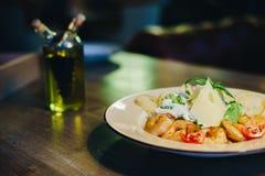 Ny caesar sallad i en rund platta på en trätabell och en flaska av olivolja Royaltyfri Bild