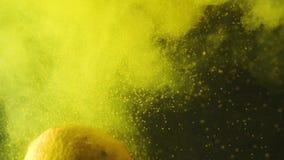 Ny citron som plaskar in i det gula vattnet med pollen Ny frukt som faller i vattnet Organiskt b?r, sund mat arkivfilmer
