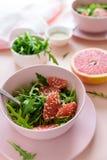 Ny citrus sallad med arugula-, grapefrukt- och sesamfrö på rosa bakgrund Selektivt fokusera Rå vegetarisk vårdetox arkivfoto