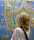 NY City subway map and tourist. NEW YORK CITY - September 25: A tourist finds her way in Manhattan with the help of the subway and bus map in Penn Station on Stock Photos