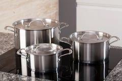 Ny cookwareuppsättning på induktionshoben royaltyfria foton