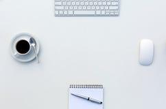 Ny dag på den vita tabellen för kontorsbegrepp med bästa sikt för för datormellanrumsNotepad och kopp kaffe arkivbild