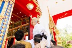 Ny förordnad munk som ber med en thailändsk procession för buddistisk munk när man över 20 gamla år royaltyfria bilder