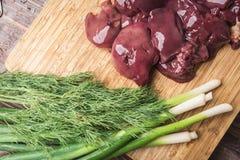 Ny feg lever, salladslökar och dill på en träskärbräda Royaltyfri Fotografi