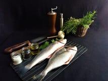 Ny fisk med citronen och kryddor p? svart royaltyfria foton