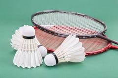 Ny fjäderboll för badminton tre med racket på den gröna matta domstolen Royaltyfri Bild