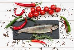 Ny forellfisk på skärbräda med körsbärsröda tomater Arkivfoto