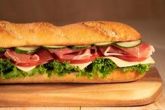 Ny frasig smörgås med prosciuttoen, ost, tomater, grönsallat, gurkor på en träbakgrund close upp sunt begrepp royaltyfri fotografi