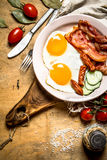 Ny frukostplatta baconägg stekte tomater Arkivbild