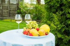 Ny frukt på en platta och en vinglas med vitt vin på en tabell i trädgården royaltyfria foton