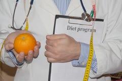 Ny frukt som mäter bandet med, bantar plan Sund matmarknadsföring Vegetariska grönsaker bantar Stående av den manliga dietisten W Royaltyfri Foto