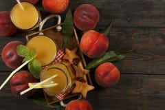 Ny fruktsaft för persika med nya persikor på en mörk bakgrund Bästa sikt, kopieringsutrymme äta som är sunt Ny fruktsaft med pers Royaltyfri Bild