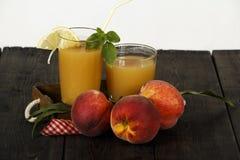 Ny fruktsaft för persika med nya persikor på en mörk bakgrund Bästa sikt, kopieringsutrymme äta som är sunt Ny fruktsaft med pers Royaltyfri Foto