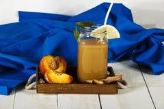 Ny fruktsaft för persika med nya persikor på en vit bakgrund Bästa sikt, kopieringsutrymme Ny fruktsaft med persikan Ny persika f Royaltyfri Bild