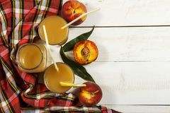 Ny fruktsaft för persika med nya persikor på en vit bakgrund Bästa sikt, kopieringsutrymme Ny fruktsaft med persikan Ny persika f Royaltyfri Fotografi