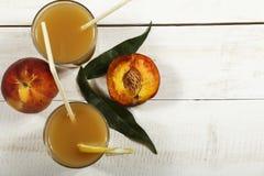 Ny fruktsaft för persika med nya persikor på en vit bakgrund Bästa sikt, kopieringsutrymme Ny fruktsaft med persikan Ny persika f Arkivbild