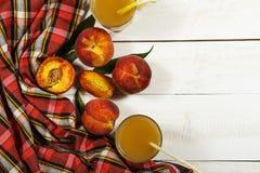 Ny fruktsaft för persika med nya persikor på en vit bakgrund Bästa sikt, kopieringsutrymme Ny fruktsaft med persikan Ny persika f Arkivbilder