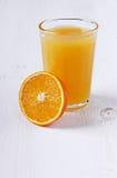 Ny fruktsaft i ett exponeringsglas med en orange halva Royaltyfri Foto