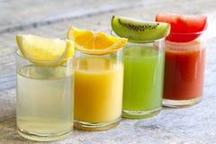 Ny fruktsaft i exponeringsglas med skivor av frukter Arkivbild