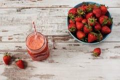 Ny fruktsaft, skaka, milkshake av jordgubbar i en murarekrus med ett sugrör Hög av saftiga mogna organiska nya jordgubbar i en la arkivbilder