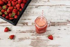 Ny fruktsaft, skaka, milkshake av jordgubbar i en murarekrus med ett sugrör Hög av saftiga mogna organiska nya jordgubbar i en bl royaltyfri foto