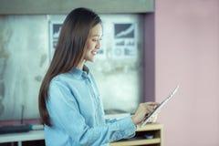 Ny generationaffärskvinnan arbetar med en minnestavla, asiatisk wom arkivfoton