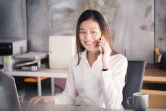Ny generationaffärskvinnan som använder smartphonen, den asiatiska kvinnan, är H royaltyfri fotografi