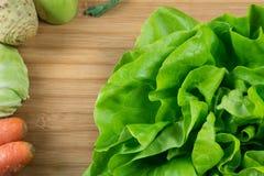 Ny grön grönsallat på torskbrädet och nya grönsaker, morot, kål, selleri och kålrabbi på sidan arkivfoto