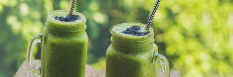 Ny grön smoothie för BANER med bananen och spenat med hjärta av sesamfrö Förälskelse för ett långt format för sunt råkostbegrepp royaltyfri fotografi